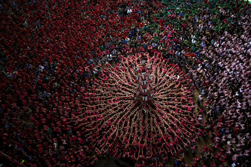"""Members of """"Vella de Xiquets de Valls"""" try to complete their human tower during the 26th Human Tower Competition in Tarragona, Spain, on Sunday, Oct. 2, 2016. The tradition of building human towers, or Castells, dates back to the 18th century and takes place during festivals in Catalonia, where """"colles"""", or teams, compete to build the tallest and most complicated towers. The structure of the castells varies depending on their complexity. A castell is considered completely successful when it is loaded and unloaded without falling apart. The highest castell in history was a 10 floor structure with 3 people in each floor. In 2010 castells were declared by UNESCO one of the Masterpieces of the Oral and Intangible Heritage of Humanity. (AP Photo/Emilio Morenatti)"""