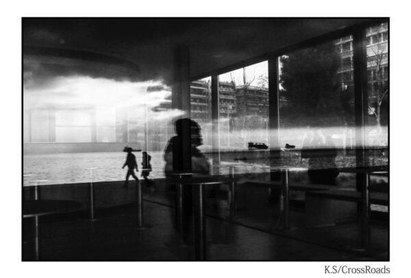 Reflection of people seeking refuge in glass window