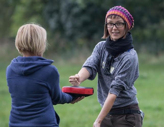 Self-defence trainer Kinga Karp wearing a colourful hat and smiling and practicing punching technique with a trainee outside on a field.