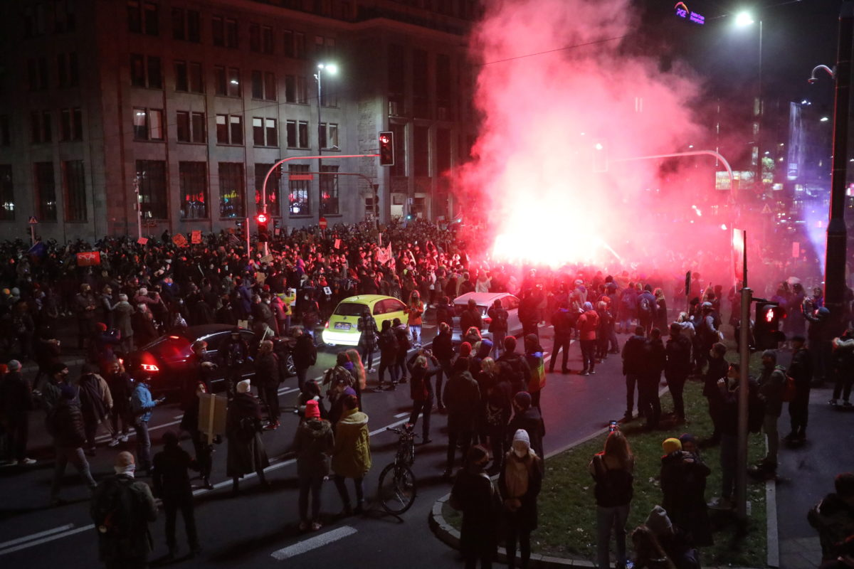 A street in Warsaw at night filled with women protesters with a pink flare and smoke in the background.