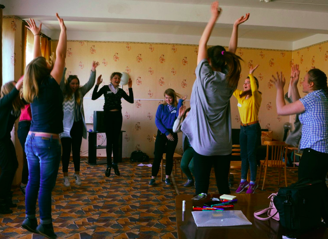 A group of young teenagers leaping into the air and jumping, practicing self-defence moves.