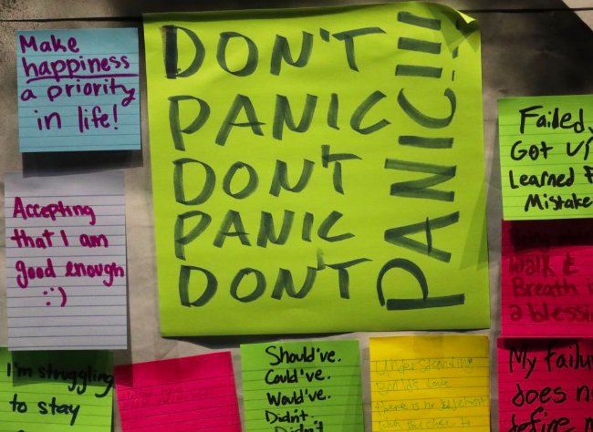 """A board covered in colourful post-it notes from a training session with handwritten statements saying things like """"Don't Panic"""", """"Make happiness a priority in life"""", """"Accepting that I am good enough"""" and """"Failed, got up and learned from mistakes"""""""