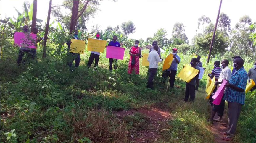 A group of activists from Uganda stand in a circle holding large colourful placards handwritten with slogans.